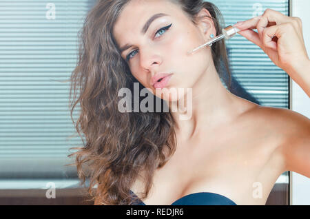 young beautiful curly woman uses serum for face. The concept of facial skin care. - Stock Photo