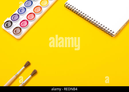 Watercolor paints and brushes with canvas for painting with copyspace on yellow background