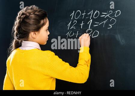 schoolgirl in yellow sweater writing on blackboard with chalk - Stock Photo