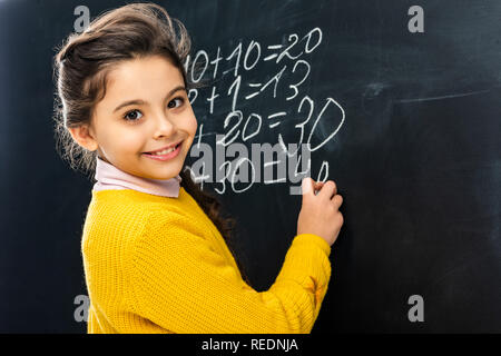 smiling schoolgirl writing on blackboard with chalk and looking at camera - Stock Photo