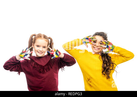 cheerful schoolgirls smiling, showing hands painted in colorful paints and looking at camera isolated on white