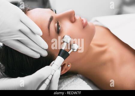 Beautiful woman receiving facial microcurrent procedure for rejuvenation skin. - Stock Photo