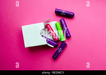 white box with multi-colored tampons on a pink background - Stock Photo