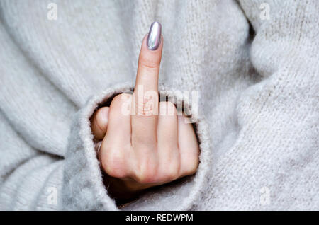 a woman in a sweater shows a gesture. Nails with a metal coating. - Stock Photo