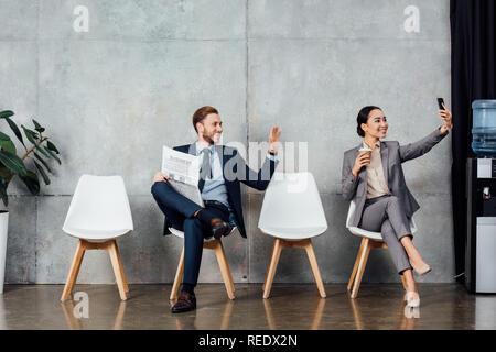 businessman with newspaper waving with hand while asian businesswoman taking selfie on smartphone in waiting hall - Stock Photo