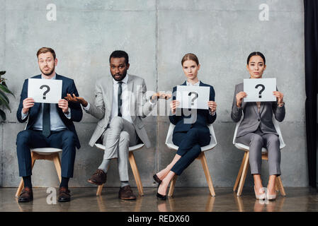 multiethnic businesspeople holding cards with question marks in waiting hall - Stock Photo