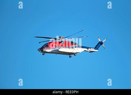 A Sikorsky S92-A helicopter from the Babcock MCS Offshore/Onshore fleet at Aberdeen arriving back at Dyce heliport from the North sea crossing. - Stock Photo