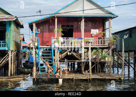 Children playing outside a house on stilts in floating village in Tonle Sap lake. Kampong Phluk, Siem Reap province, Cambodia, southeast Asia - Stock Photo