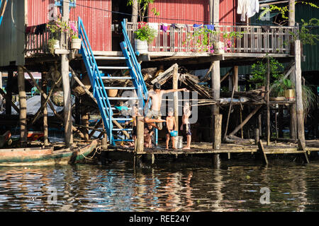 Children playing outside a house on stilts in floating village in Tonle Sap lake. Kampong Phluk, Siem Reap province, Cambodia, Asia - Stock Photo