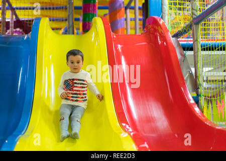 Little boy is going down a slide at the playground. He is laughing and having fun on the jungle gym. Boy riding from childrens slides on playground - Stock Photo