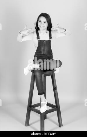 Girl smile with pointing fingers on blue background. Child in jeans overall sit on high wooden chair. Happy childhood concept. Presenting product, promotion, advertising. Fashion, beauty, look. - Stock Photo