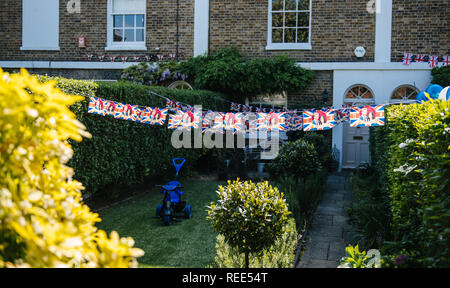 WINDSOR, BERKSHIRE, UNITED KINGDOM - MAY 19, 2018: Backyard party with party flags rpinted with facess of Prince Harry and Meghan Markle - Windsor house on the Royal Wedding day - Stock Photo
