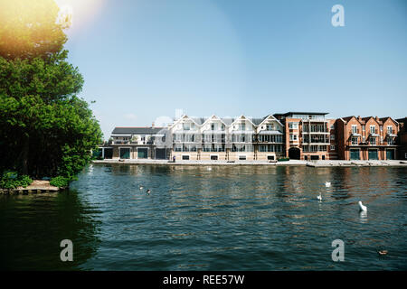 WINDSOR, BERKSHIRE, UNITED KINGDOM - MAY 19, 2018: Luxury houses on Tamisa river with swans and blue clear sky - Stock Photo
