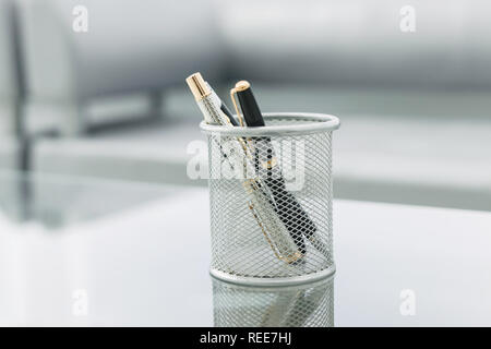pencil stand and glasses on the glass Desk in the office - Stock Photo