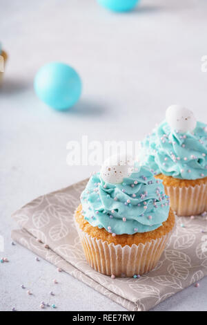 Easter vanilla cupcakes with cream cheese frosting and candy eggs. - Stock Photo