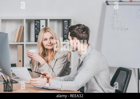 professional businesspeople working with papers and looking at each other while sitting together at desk - Stock Photo