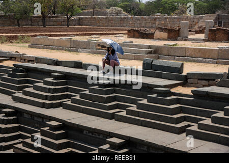 Female Indian tourist sitting with an umbrella at the public bath and the royal enclosure step water well in Hampi, Karnataka, India. - Stock Photo