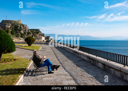Greece Corfu Corfu Town an elderly couple sits along the seafront near the Old Fortress taking in the sun - Stock Photo