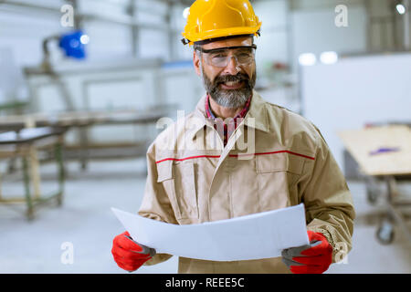 Handsome mature engineer looking at a plan in the factory - Stock Photo