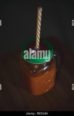 Fresh juicy in mason jar with a straw - Stock Photo