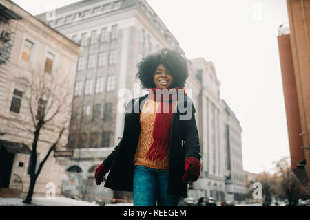 Happy young black woman is walking to the city street and smiling. Closeup.