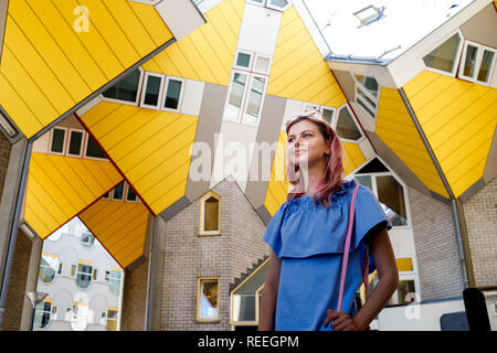 the girl on the background of the cube house or Kubuswoningen in Dutch are a set of innovative houses designed by architect Pete Blom and built in Rot - Stock Photo