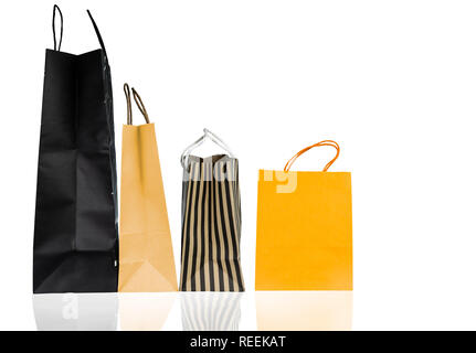 Four paper shopping bags isolated on white background. Shopping bag with blue, brown, and yellow color. Discount sales concept. Gift bag. Consumerism  - Stock Photo