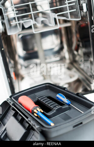 Toolbox in front of domestic dishwasher in the kitchen. - Stock Photo