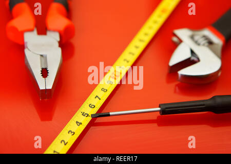 Pliers, tape measure, flex-head wrench and screwdriver-tap lie on the red polished surface in the auto repair shop. Tools mechanics. Performance of wo - Stock Photo