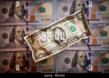 Two crumpled dollars on a blurred background of bills worth one hundred dollars the new American bill. - Stock Photo
