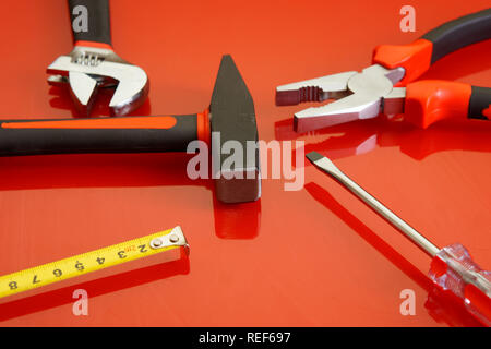 Pliers, tape measure, screwdriver, hammer and adjustable wrench lie on a red polished surface. Tools for the mechanic. - Stock Photo