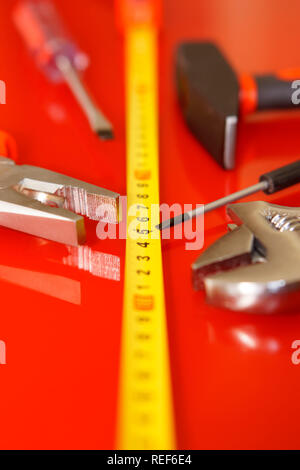 Screwdriver, pliers, tape measure, hammer and adjustable wrench lie on a red polished surface. Tools for the mechanic. Shallow depth of field. Vertica - Stock Photo