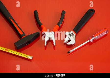 Hammer, screwdriver, pliers, tape measure and adjustable wrench lie on a red polished surface. Tools for the mechanic. - Stock Photo