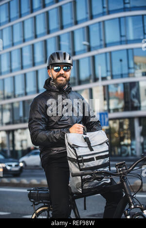 Male bicycle courier with backpack and sunglasses delivering packages in city. - Stock Photo