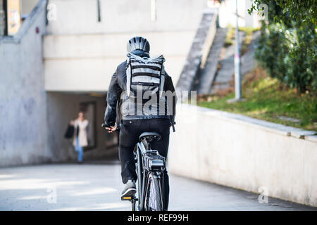 A rear view of male bicycle courier delivering packages in city. Copy space. - Stock Photo
