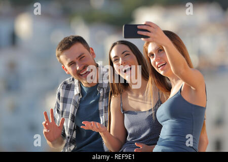 Three happy friends taking selfies with a smart phone outdoors in a town outskirts at sunset - Stock Photo