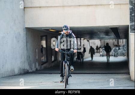 Male bicycle courier delivering packages in city. Copy space. - Stock Photo