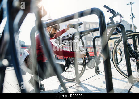 Hipster businessman commuter parking electric bicycle in city when going to work. - Stock Photo