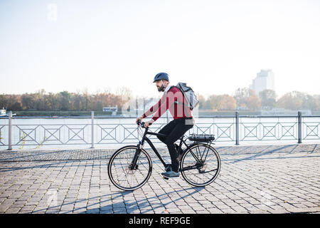 Hipster businessman commuter with electric bicycle traveling to work in city. - Stock Photo
