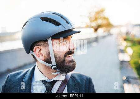 Businessman commuter with bicycle helmet traveling home from work in city. - Stock Photo