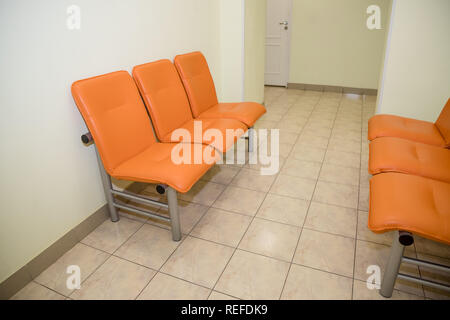 empty seats at a business building against a wall, interior setting.Waiting area with seats in a clinic.Empty orange chairs in waiting room.Office Entrance Area interior.hospital lobby with chairs for patients,doctor visit. - Stock Photo