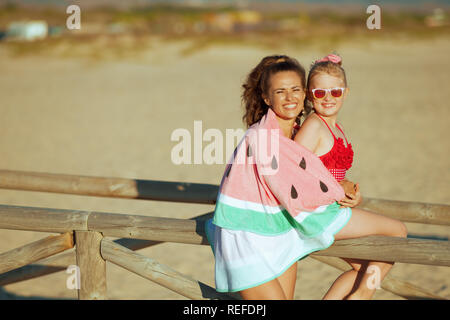 smiling modern mother and daughter in swimwear on the ocean shore in the evening wrapped in watermelon towel. mother and daughter near a wooden fence. - Stock Photo