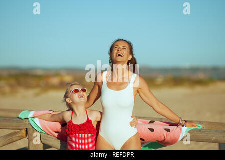 smiling young mother and daughter in swimwear on the beach in the evening having fun time. mother and daughter near a wooden fence. sand and water goo - Stock Photo
