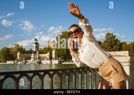 smiling elegant traveller woman in white blouse and shorts at El Retiro Park in Madrid, Spain using a smartphone and waving to someone or local young  - Stock Photo