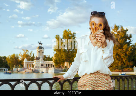 cheerful young traveller woman in white blouse and shorts at El Retiro Park in Madrid, Spain looking through traditional Spain churro. you can't leave - Stock Photo