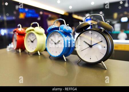 Retro alarm clock on the table in a row - Stock Photo