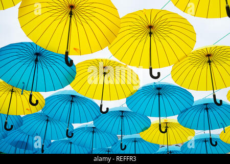 Umbrellas float in sky on sunny day. Umbrella sky project installation. Outdoor art design and decor. Holiday and festival celebration. Shade and protection.
