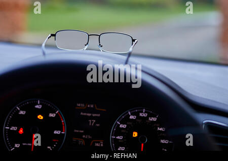Pair of glasses on dashboard of car - Stock Photo