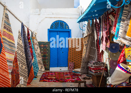 Traditional Tunesian carpets hanging on blue walls in resort town Sidi Bou Said. Tunisia, North Africa. - Stock Photo