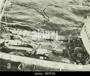 """. Commercial fisheries review. Fisheries; Fish trade. Fig. S - Twice in less than 3 weeks, crew of U. S. Coast Guard cutter Storis (W 38} stopped and boarded a Soviet shrimp trawler violating U, S, fishery laws off Alaska. Storis is shown prepar- ing to lower boat with boarding party. The medium freezer trawler SRTM-8457 (foreground), is watched by a Coast Guard aircraft, from which photo was taken. On March 22, a Coast Guard aircraft sighted a Soviet fishing vessel 5.5 miles east of Seal Cape (Alaska) and identified it as """"SRTM- 8457."""" The vessel had nets in the water and thus was f - Stock Photo"""